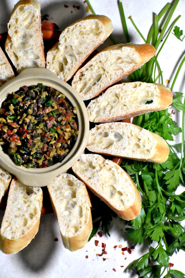 A small white dish of tapenade accompanied by sliced baguette bread.