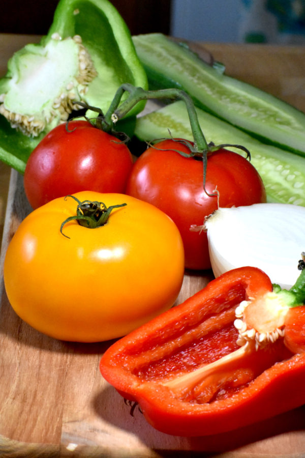 tomatoes, peppers, onion and cucumber on a cutting board