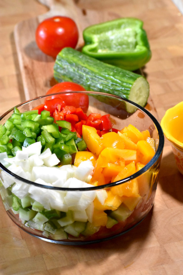 chopped tomatoes, peppers, onions and cucumber in a glass bowl