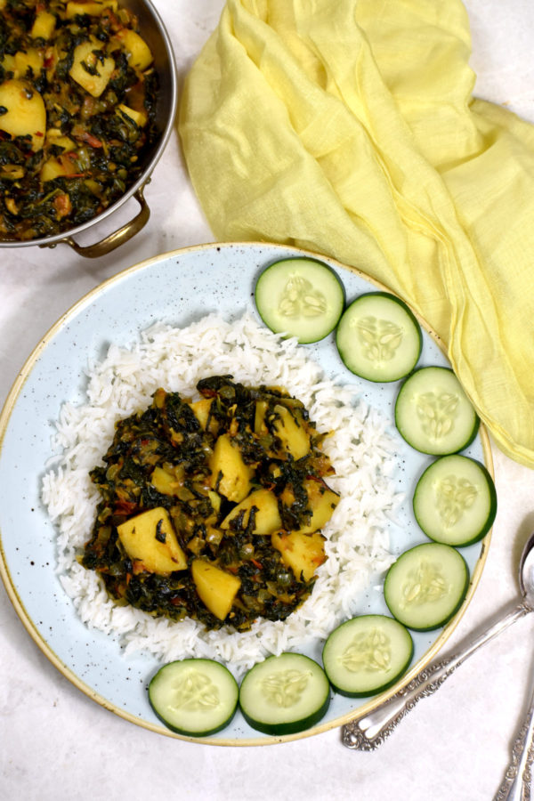 Aloo Palak arranged atop a bed of white rice and garnished with sliced cucumbers.
