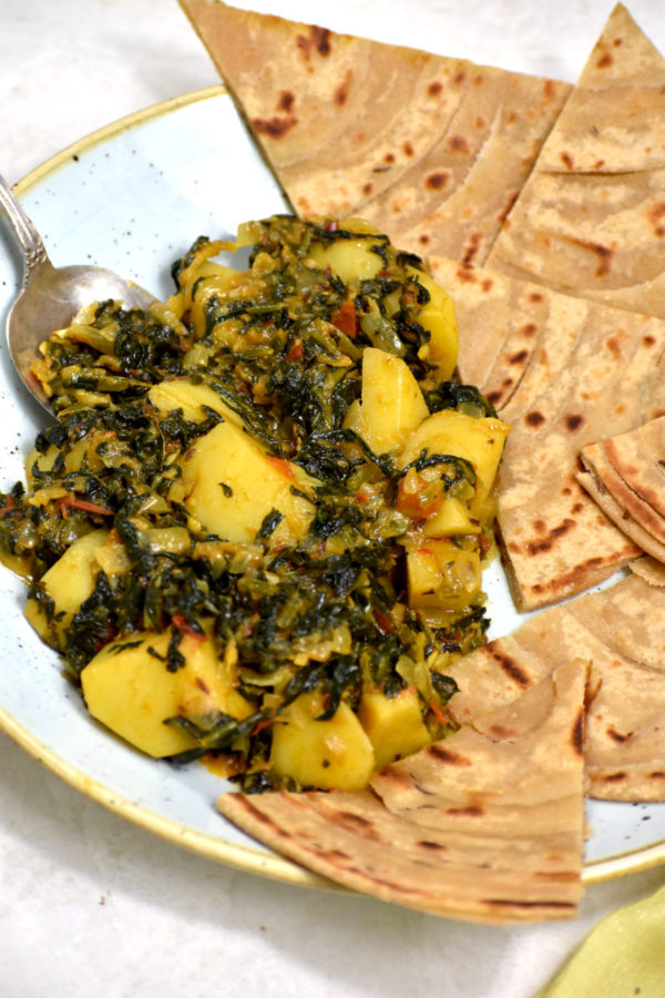 Side view of our sauteed spinach and potatoes with rotis.