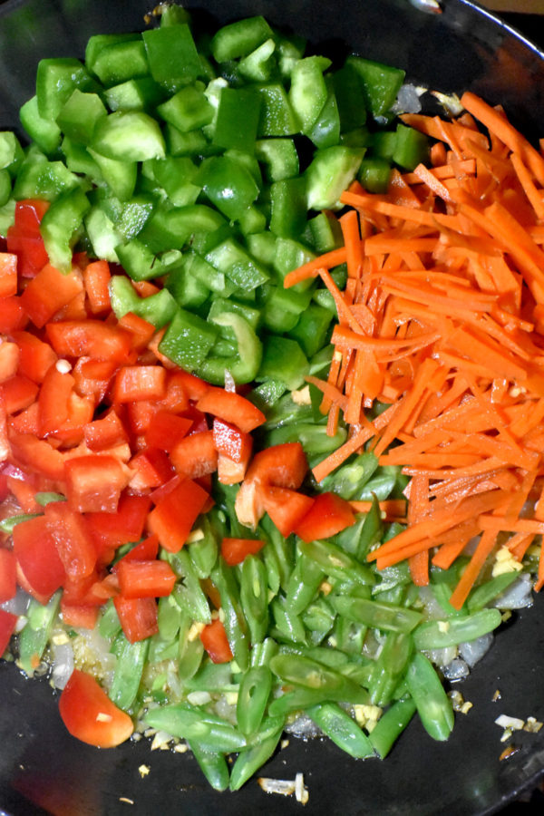 Chopped bell peppers, carrots and green beans added to the pan.