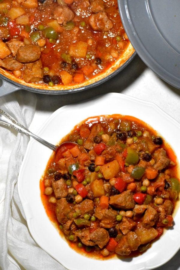 The bowl of menudo alongside a dutch oven.
