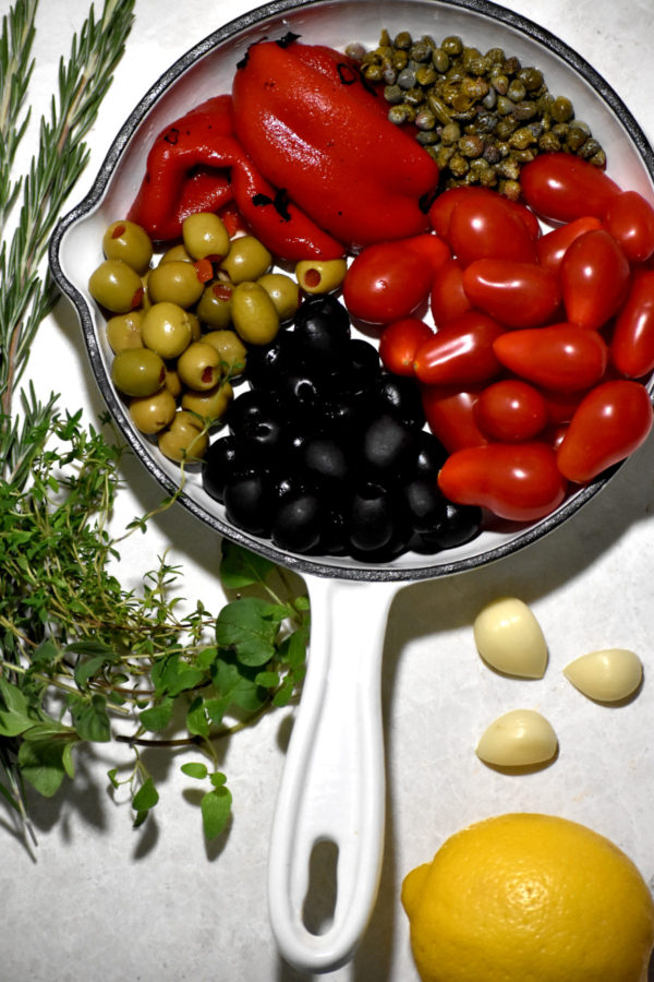 Ingredients for tapenade arranged on a white background.