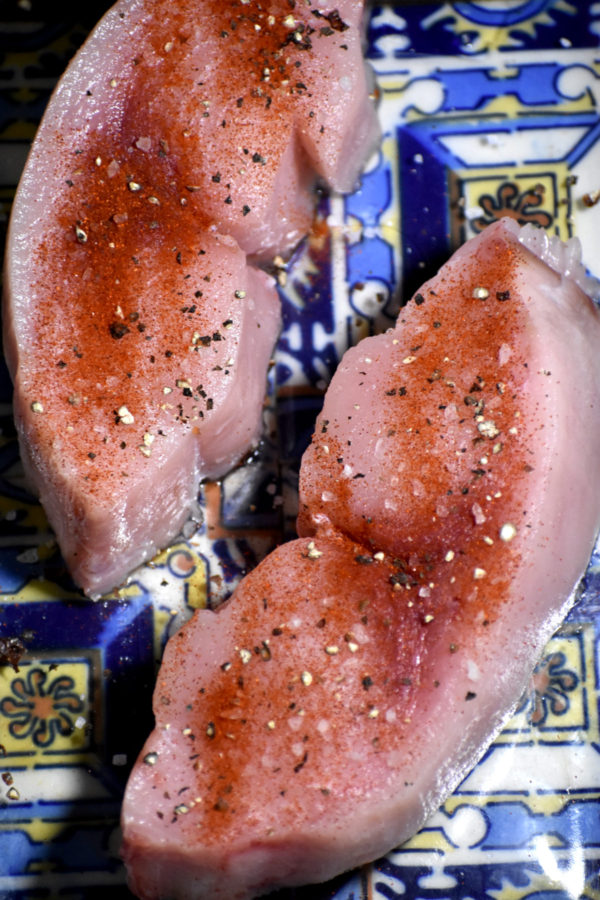 Two pieces of swordfish dusted with salt, pepper and paprika.