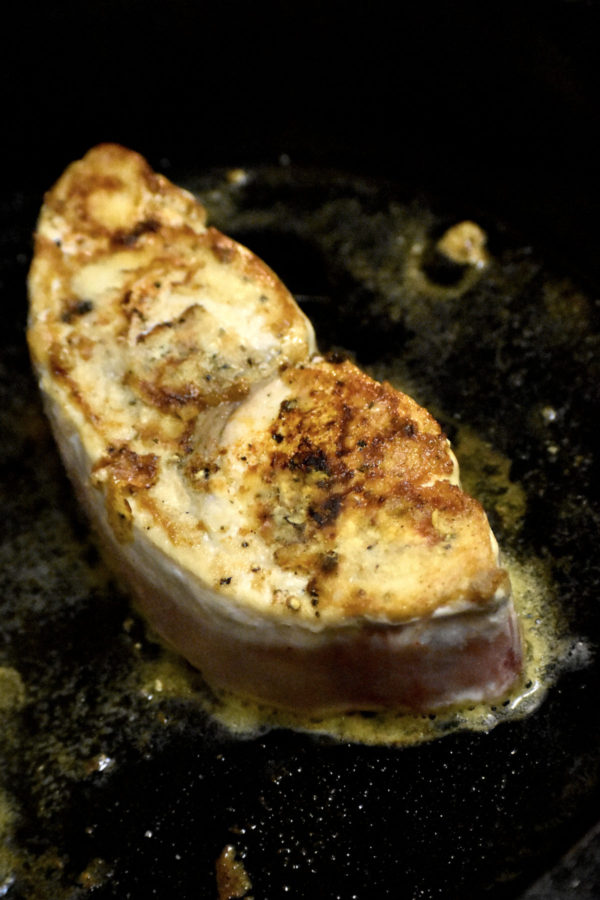 Piece of swordfish cooking in a cast iron skillet.
