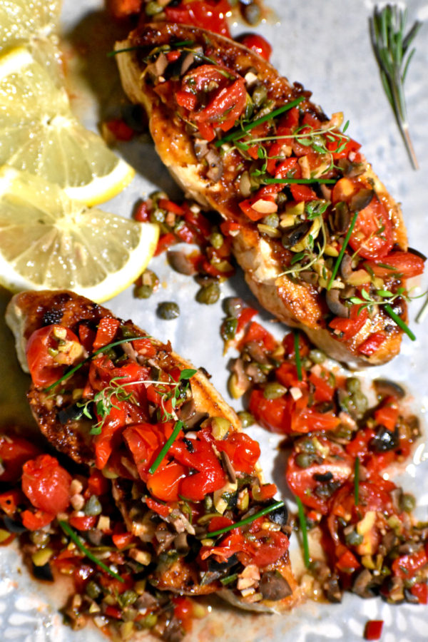 Overhead shot of two pieces of cooked fish topped with tapenade.