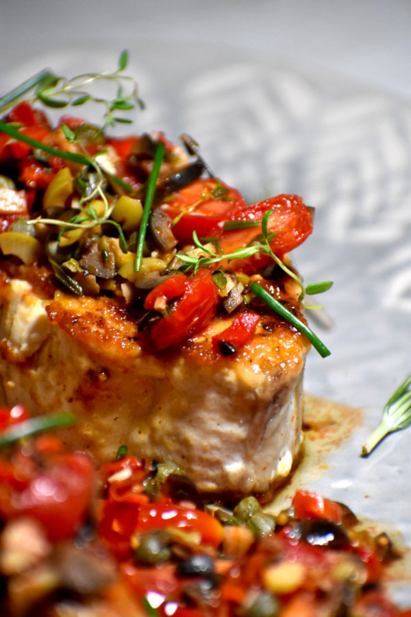 Side view of Mediterranean fish topped with tapenade.