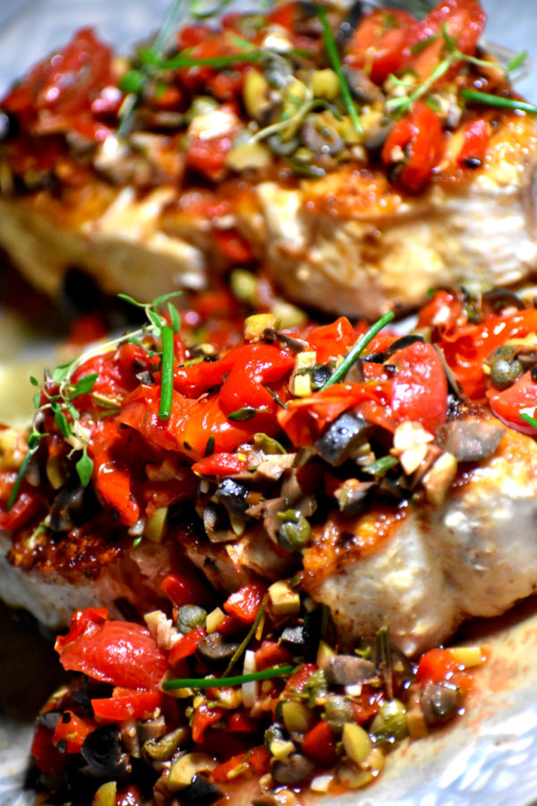 Side view of a nice slab of seared swordfish topped with tapenade.