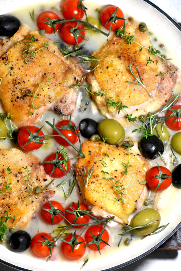Close up of the chicken, olives and tomatoes in the wine sauce, prior to baking.