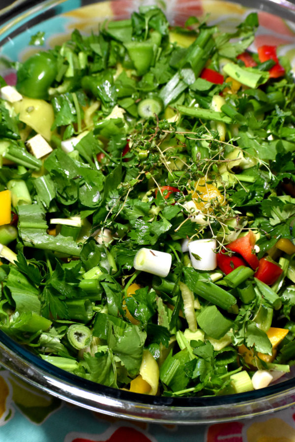 Chopped veggies and herbs in a glass bowl.