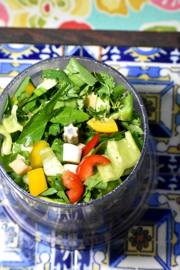 Chopped veggies and herbs in a blender.
