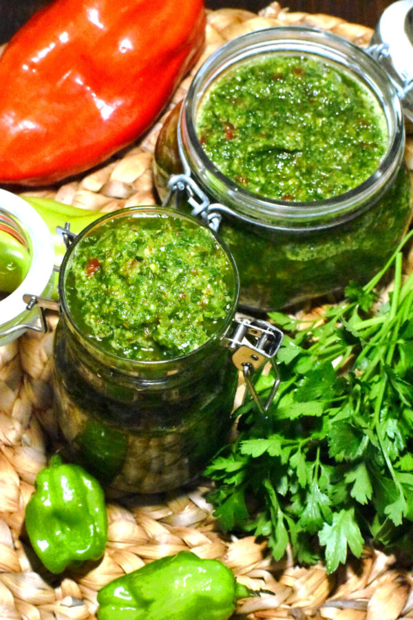 Overhead shot of two mason jars full of green seasoning, surrounded by peppers and herbs.