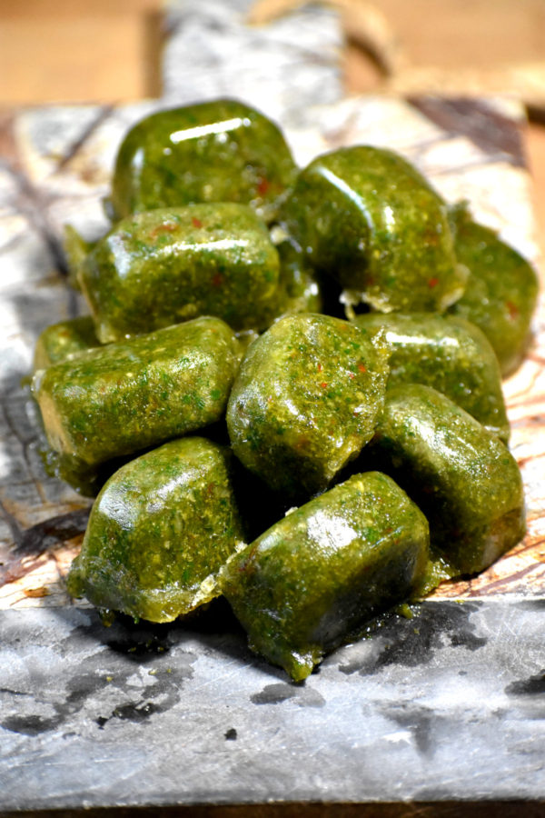 A pile of frozen cubes of green seasoning on a stone cutting board.