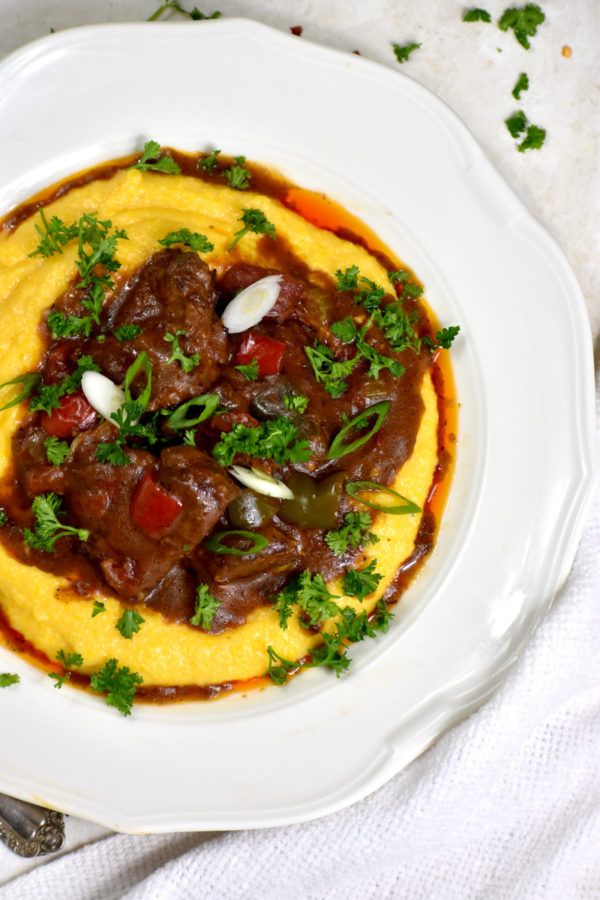 Close up of a bowl of grillades over grits and garnished with parsley and scallions.