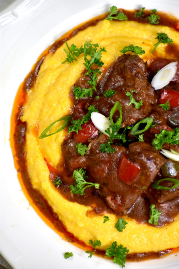 Close up of braised beef medallions in gravy over cheesy grits.