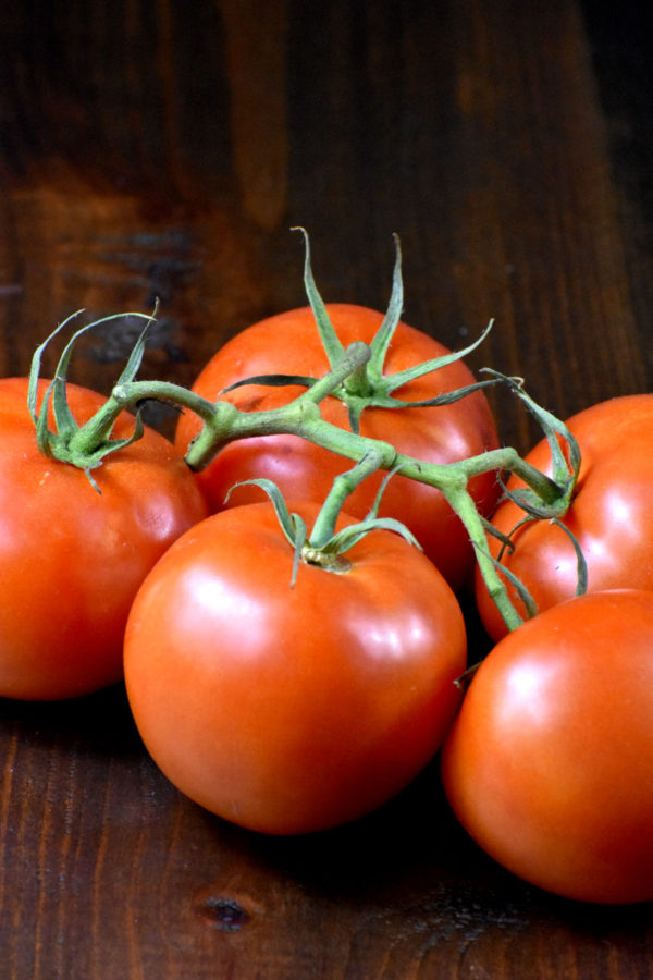 Some on-the-vine tomatoes on a wooden platform.