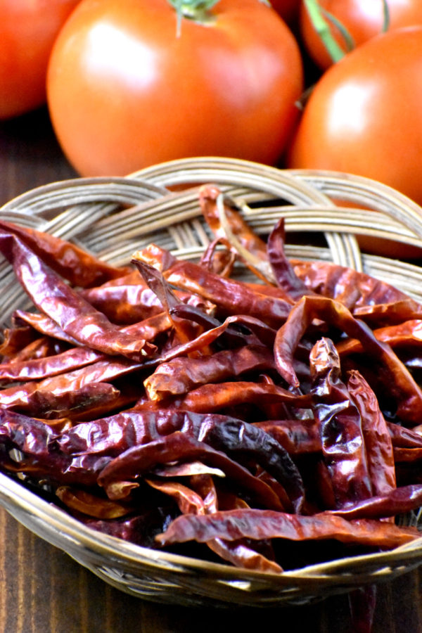 A bunch of dried arbol chilis in a wicker bowl.