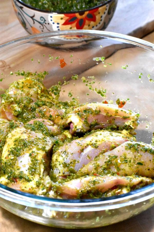 Chicken pieces marinating in green seasoning.