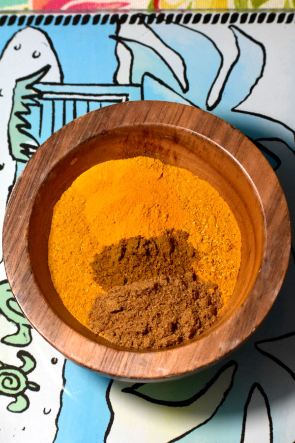Spice powders in a small wooden bowl.
