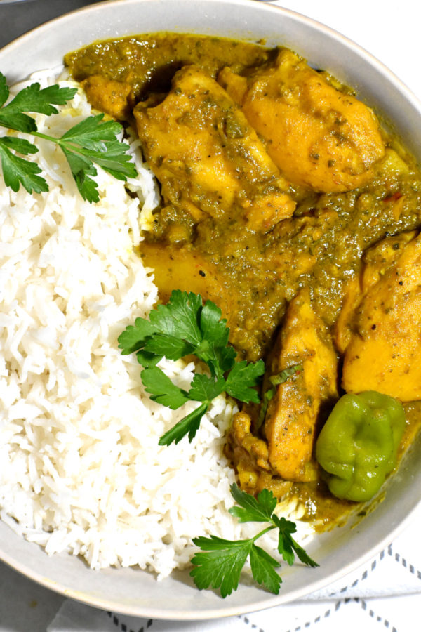 A bowl of Trinidadian curry chicken in a bowl alongside white rice.