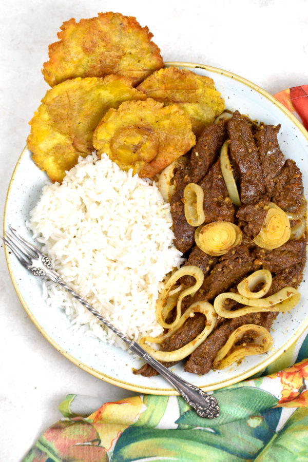 A plate of steak with onions alongside white rice and tostones.