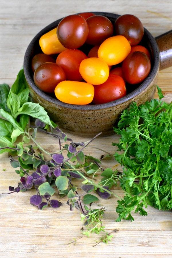 A small bowlful of cherry tomatoes alongside fresh herbs.
