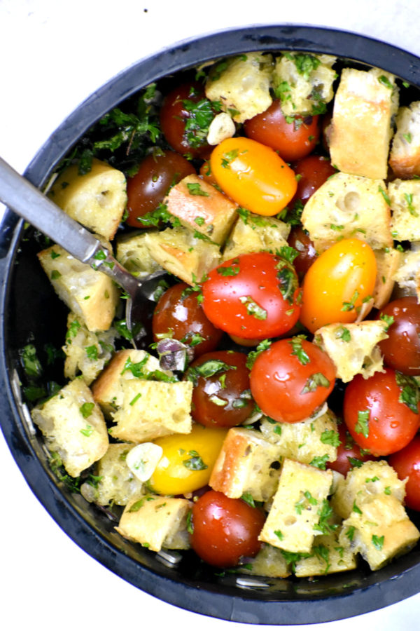 Tomatoes, bread and herbs tossed together in a bowl.