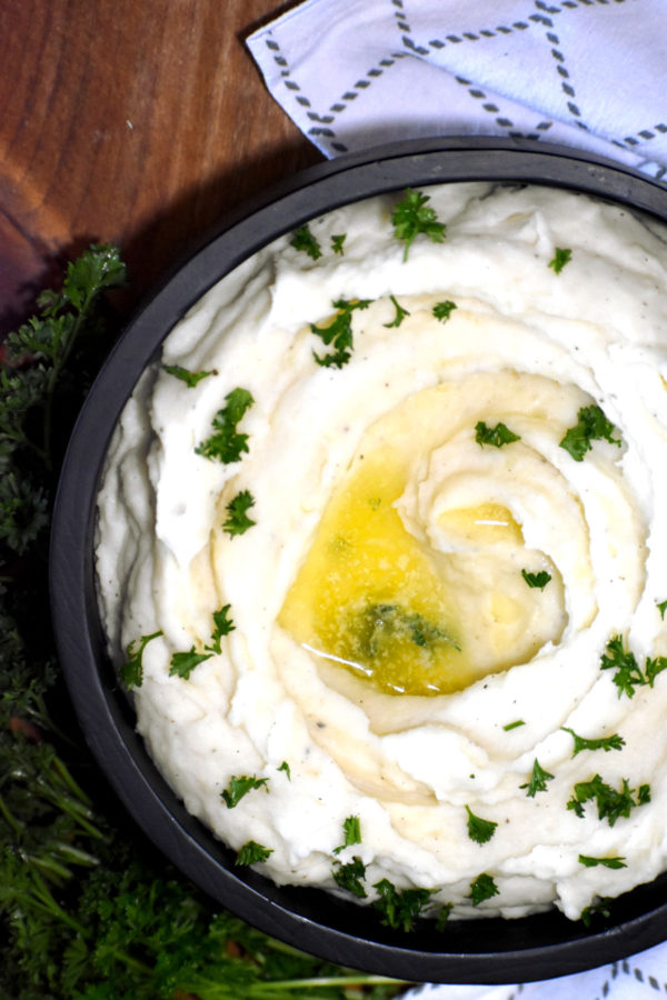Black bowl full of goat cheese mashed potatoes garnished with parsley and lots of butter.