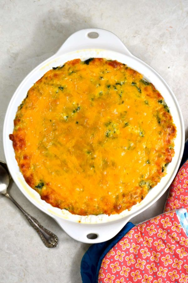 Cooked green rice casserole in a white cast iron skillet.