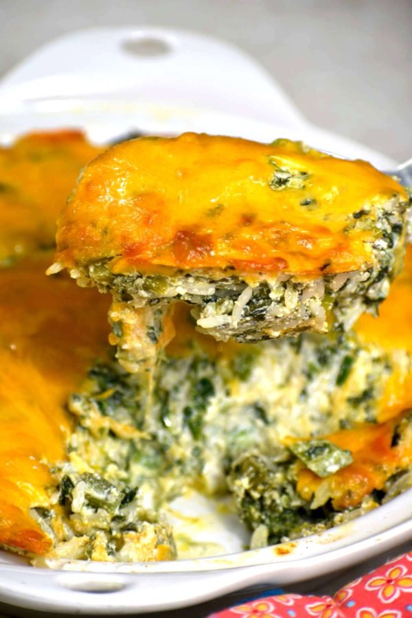 Spoon scooping a serving of this green rice casserole.