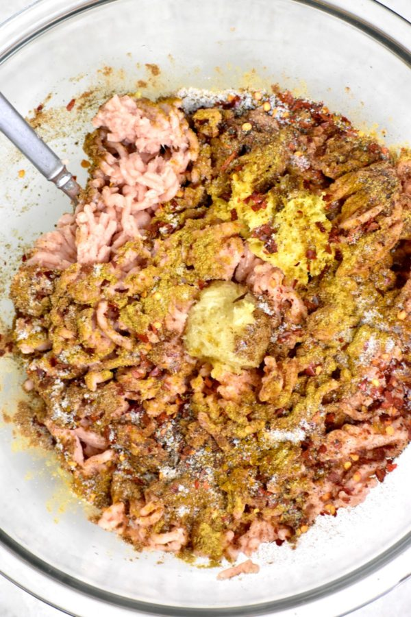 A bowl full of ground chicken topped with spices.