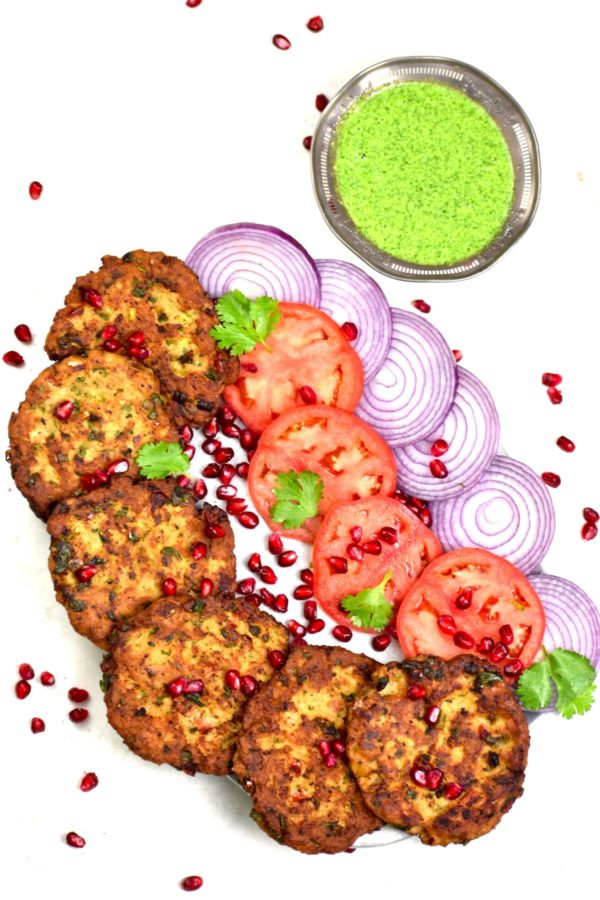 A platter of chapli kababs alongside sliced onion and tomato.
