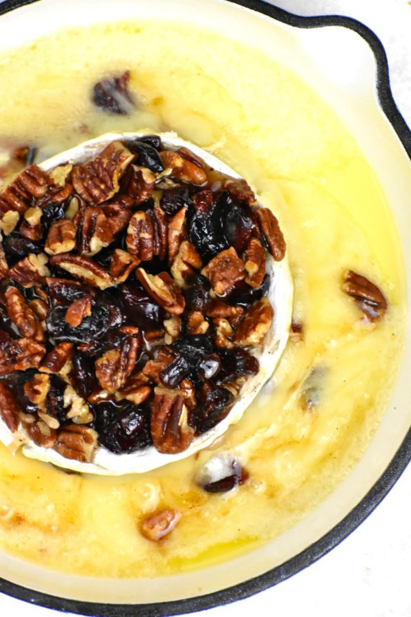 Melty baked brie topped with pecans and cranberries in a little white cast iron pan.