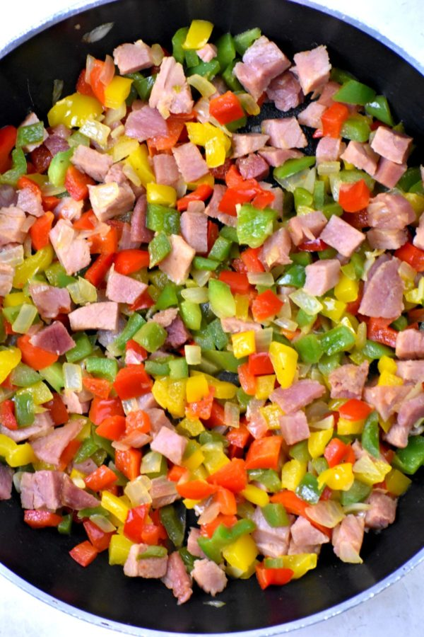 Diced ham, onions and colorful bell peppers in a skillet.
