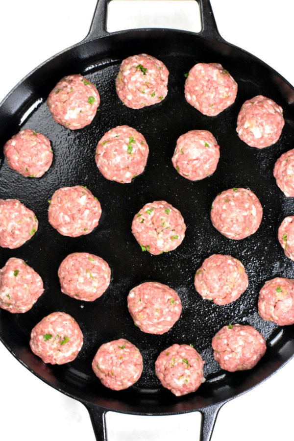 A bunch of uncooked meatballs in a cast iron skillet.