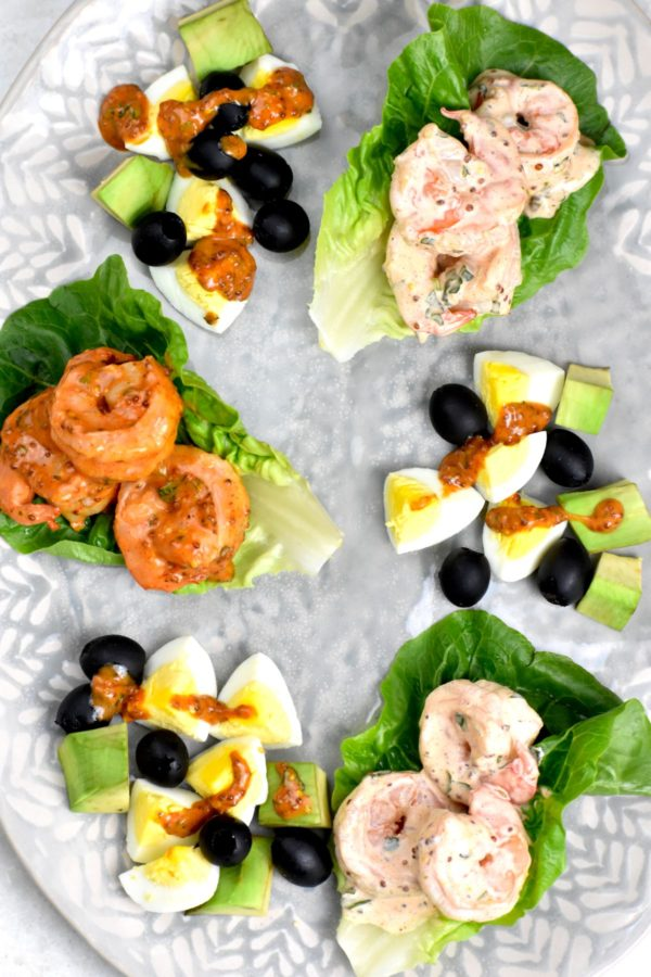 Three shrimp remoulade lettuce cups on a platter, two using the pink version of the sauce and one using the red, alongside garnishings of olives, hard boiled eggs and avocado.