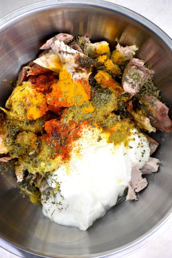 Turkey marinating in a metal bowl.