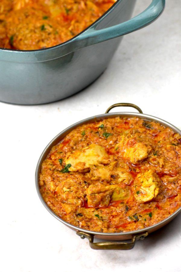 Small bowlful of turkey tikka masala with pot in background.