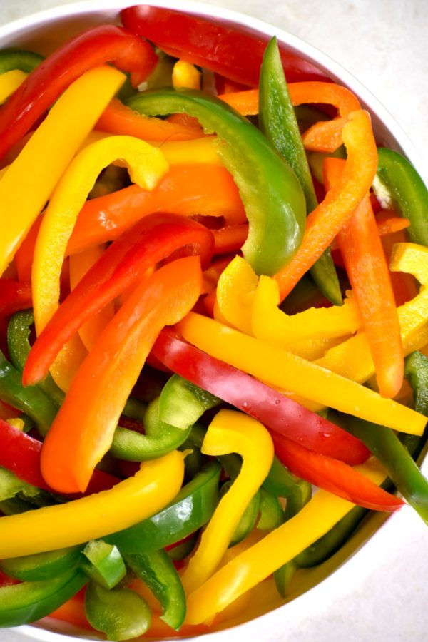 Sliced, multi colored, bell peppers in a white bowl.