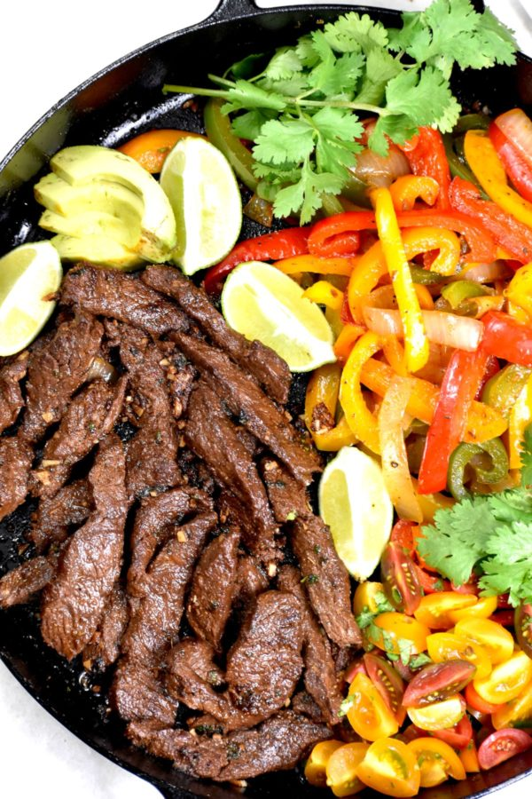 A skillet of cooked beef strips, peppers and onions.