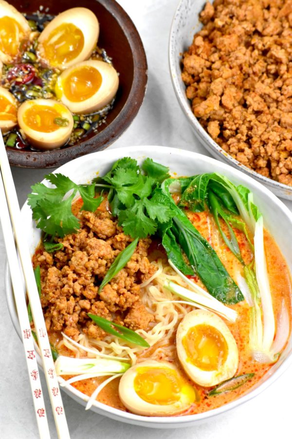 A bowl of this pink colored soup with ground pork, ramen noodles, bok choy and soft boiled eggs.