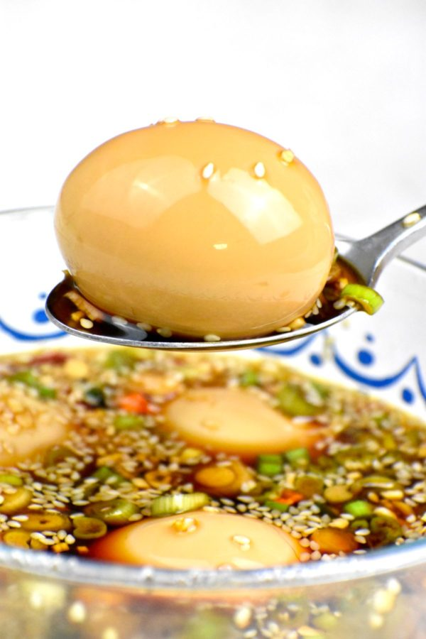 A spoon scooping an egg out of marinade.