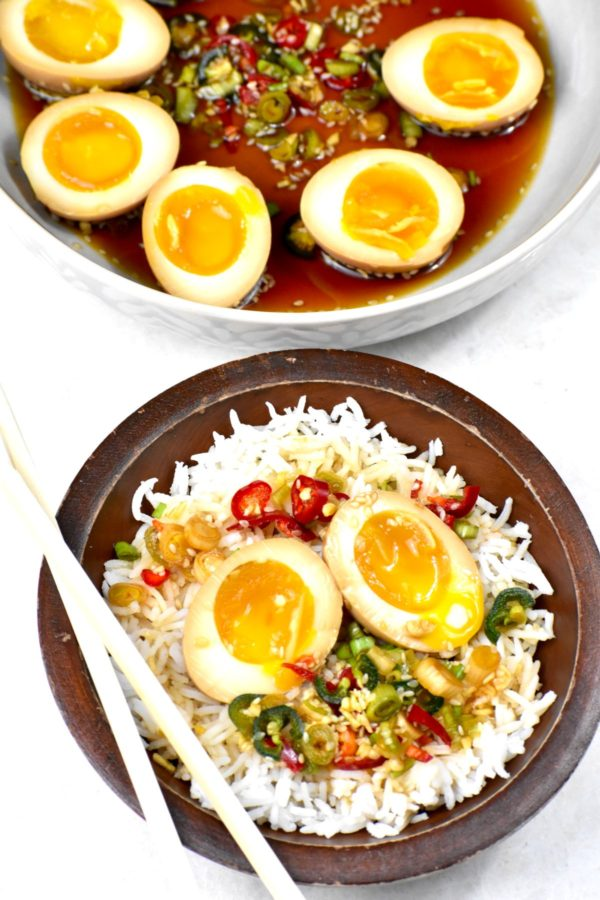 Two cut halves of these eggs atop a bowl of rice.