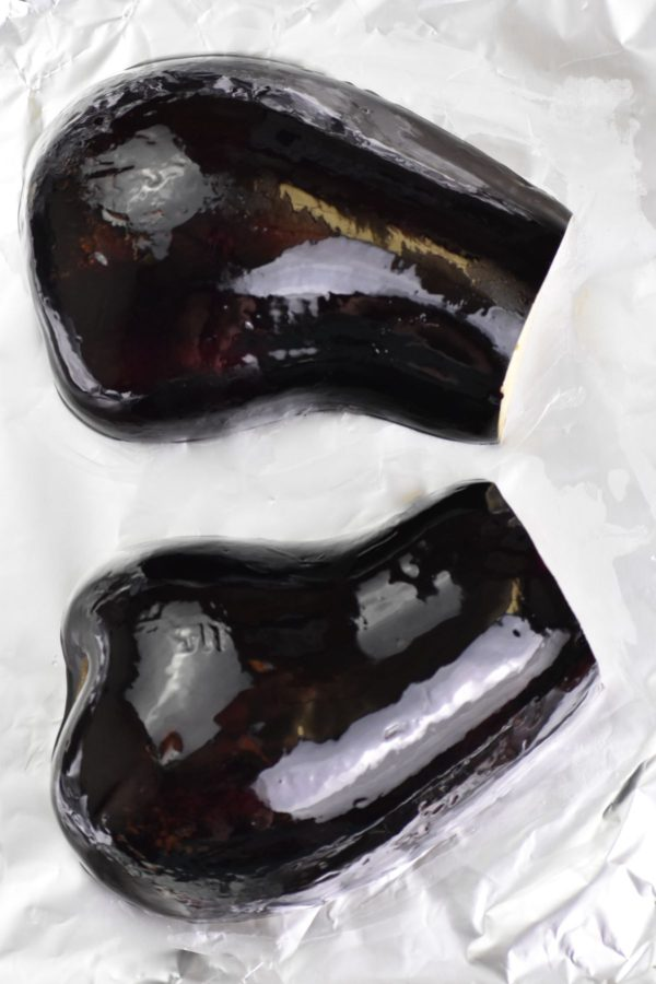 Two eggplant halves on a foil lined sheet.
