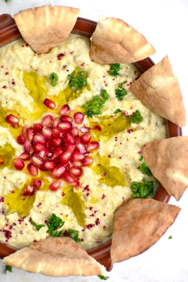 The bowl of moutabal with several pita wedges dipped in.