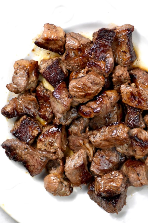 Seared bite sized pieces of steak on a plate.