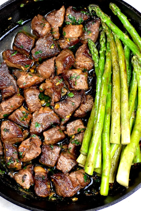 Steak bites drenched in garlic butter sauce, alongside some asparagus.