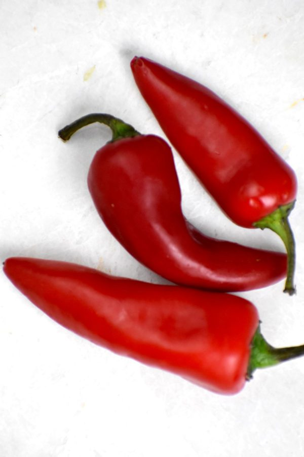 Three red chili peppers on a white background.