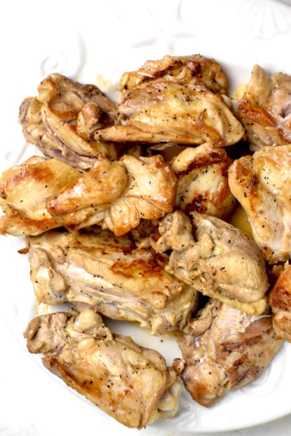 Cooked chicken pieces on a white plate.